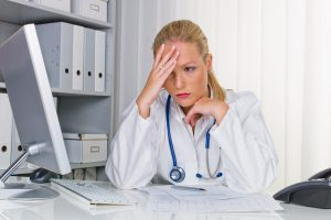 A young, stressed doctor with her hand on her head