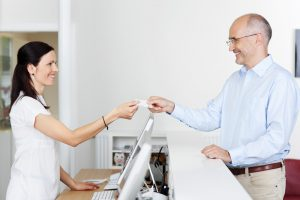 a friendly receptionist takes payment from a patient using a credit card